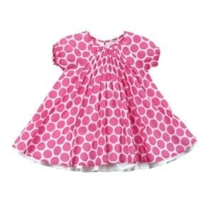 baby girls saraha dress is white with large bright pink spot pattern all over outer layer, which has centre front gather - image front view