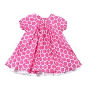 baby girls saraha dress is white with large bright pink spot pattern all over outer layer, which has centre back gather - image back view