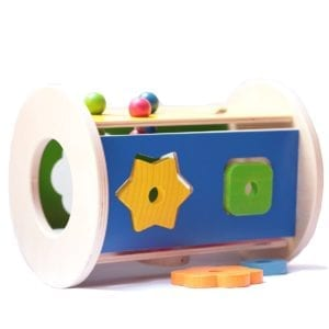 image of round shape sorter with different shape holes cut into the side for baby to place the corresponding shaped pieces through. the pieces are collected within the round container and easily shaken out through a round hole in the end of the toy.