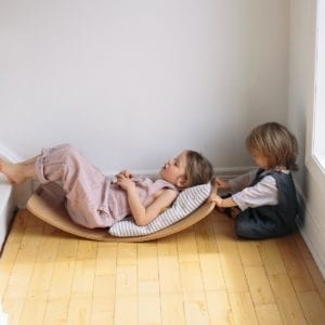 Kinderboard lifestyle image of girl lying on the board with toddler rocking her