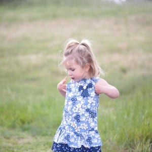 Boboli blue ruffle dress worn by little girl in the meadow - product lifestyle image