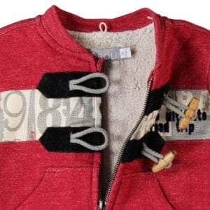 detail of toggle feature on red marl jacket
