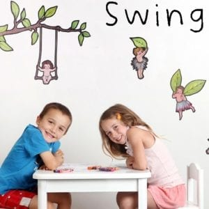 image of boy and girl sitting at a table in front of a wall decorated with illustrated girl sitting on a swing hanging from a tree branch